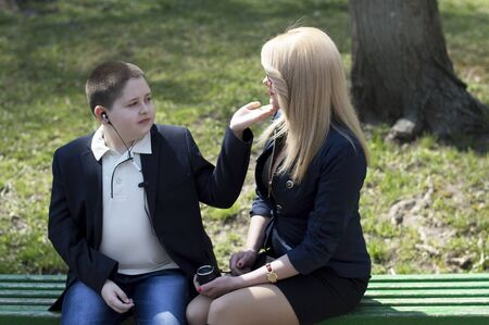 mother on bench: young mother talks to the child, sitting on a bench Stock Photo