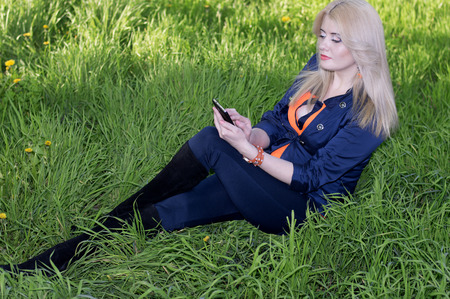 the beautiful girl on a grass with phone, a green grass photo