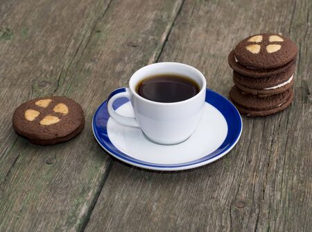 cup of coffee on an old table decorated with cookies photo