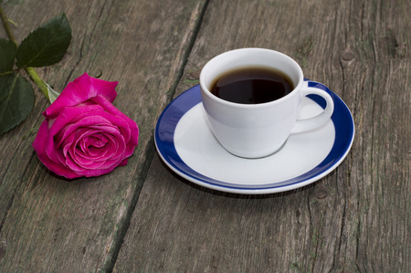 cup of coffee on an old table and nearby a rose photo