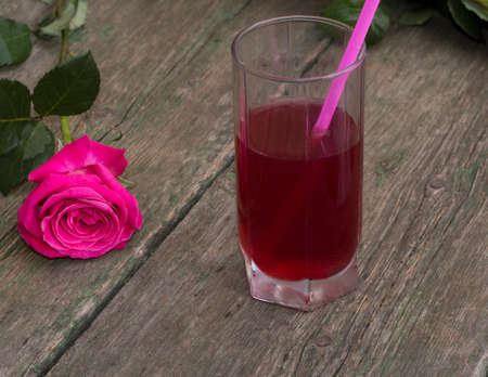 tubule: glass of red drink with a tubule nearby a rose Stock Photo