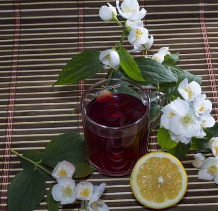 red bush tea: the red tea decorated with branches of the blossoming bush Stock Photo