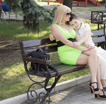 embraced: mother embraced the son sitting on a bench