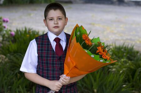 flowers boy: the lovely school student with a beautiful bouquet of flowers