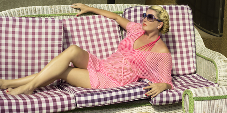 open girl: the beautiful woman in the pink has a rest on a sofa Stock Photo