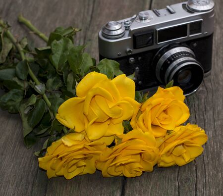 viewfinder vintage: bouquet of beautiful yellow roses and the old camera on a wooden background, a still life, a festive card, a retro the image