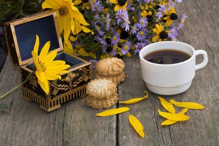 open kistje, koffie, koekjes, bloemblaadjes en wilde bloemen op een oude tafel, een stilleven, een feestelijke kaart, een wenskaart, een onderwerp drankjes en bloemen