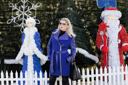 'snow maiden': the beautiful woman between the Snow Maiden and Ded Moroz against a New Year tree, a subject the woman and holidays Christmas and New Year