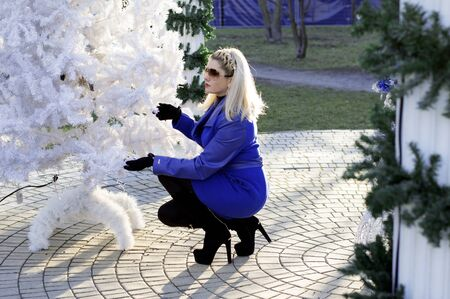 the beautiful woman in a blue coat sat down at a New Year tree, a subject the woman and holidays Christmas and New Year