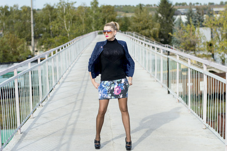miniskirt: the woman in a miniskirt on the middle of the bridge at railway station, a subject beautiful women and railway tracks Stock Photo