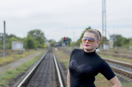 railroads: portrait of the cheerful girl in sunglasses against railway tracks, a subject beautiful women and the railroads