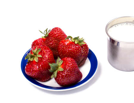 steel  milk: strawberry on a saucer and a steel mug of milk, a berry subject Stock Photo