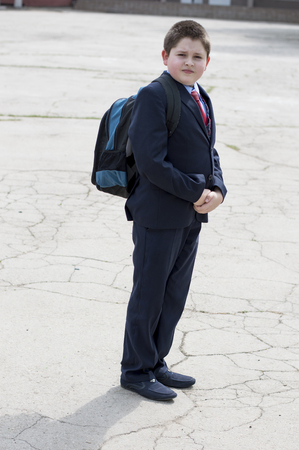 reddening: the school student with a backpack goes from school, a subject education and children