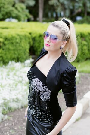 reddening: the beautiful blonde in a black suit in park, a subject beautiful women in the city Stock Photo