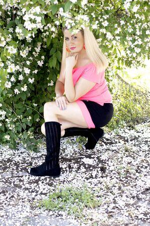 jasmine bush: the blonde in pink sits under a jasmine bush, a subject beautiful women