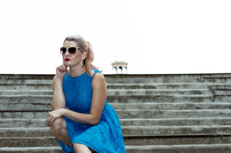 woman in the blue dress sat on the steps, the theme of beautiful vibrant women Imagens