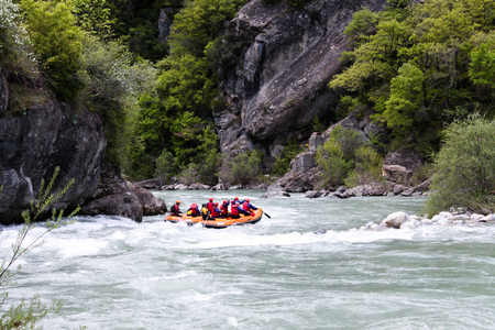 Rafting in a river of Huesca, Spain. Group of tourists in the inflatable raft