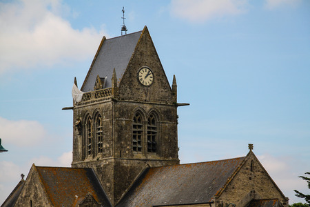 Normandy, France; 4 June 2014: The soldier landed on the steeple of the church of Sainte Mere Eglise Redactioneel