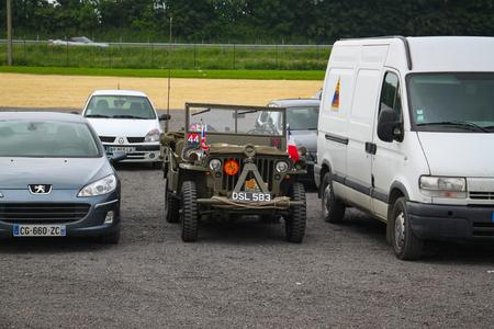 Normandy, France; 4 June 2014: U.S. Army Jeep Vehicle Used in 1944 between modern cars Redactioneel