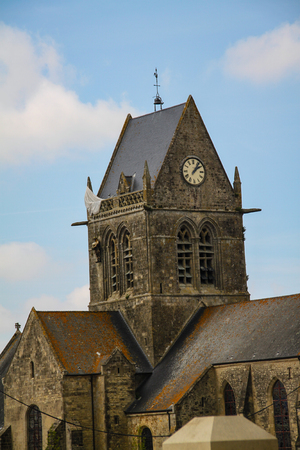 Normandy, France; 4 June 2014: Airborne paratrooper gets stuck on a church in Saint Mere Eglise in Normandy during World War II Redactioneel