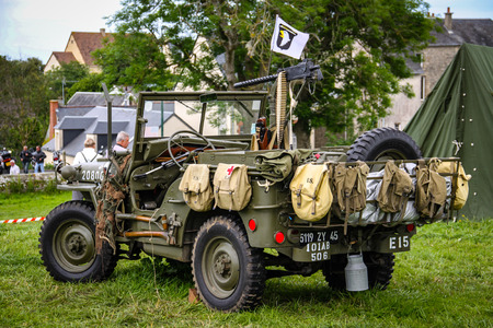 Image of an American army jeep in Normandy in a camp. Recreation on the 70th anniversary. Back view with tourists watching