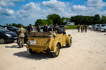 Normandy, France; 4 June 2014: Image of a kugelwagen of the German army in Normandy with the camouflage of africa korps. Recreation on the 70th anniversary. Back view with tourists watching
