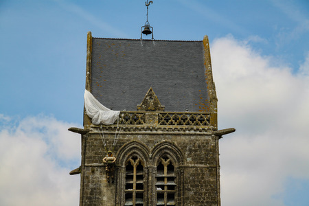 Normandy, France; 4 June 2014: The soldier landed on the steeple of the church of Sainte Mere Eglise