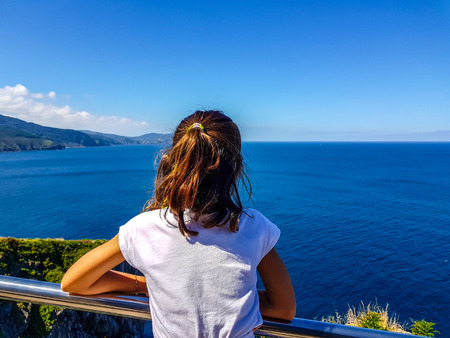 girl with her back to the blue sea leaning on a chromed railing. Unrecognizable girl