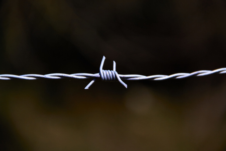 silhouette of an insulated barbed wire on a dark background