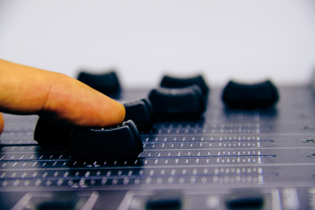 Audio mixer, mixing desk controls and fader, music mixing console with the hand of the technician moving the faders. Degraded effects for banners and backgrounds
