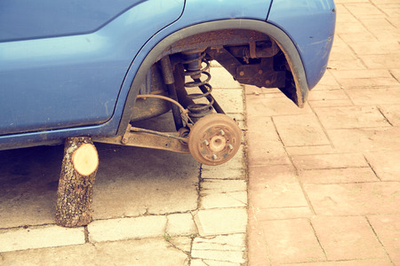 An old car waiting for the steering wheel. A car without a tyre and supported by a jack that is a wooden stump.
