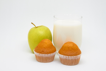 Glass of milk, piece of fruit (Apple) and cupcakes. Healthy eating concept for breakfast and a good start to the day