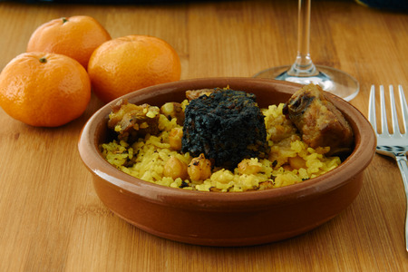 "Baked rice in a pottery dish accompanied by pork, chickpeas, blood sausage, tomato and garlic. Traditional ""arroz al horno"" from the area of Valencia, Spain"