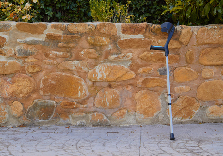 A single crutch resting on a stone wall waiting for its lame owner. Stockfoto - 122905263