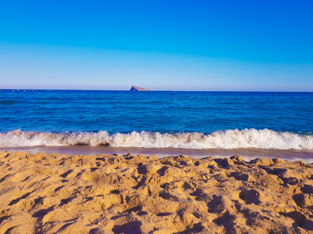 Sand on the beach with the sea and an island in the background. Picture taken on the beach of Benidorm, Spain Stockfoto