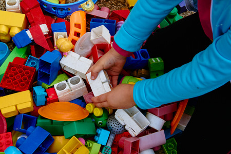 Top view on multicolored toy bricks and other toys with children's hands playing with them. Perfect for backgrounds Banque d'images - 122904998
