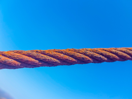 oxidized interlocked wire loop cables in the foreground with sky and sea bottoms. Image taken in Lanzarote, Spain