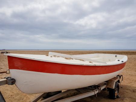 una barca a terra con i colori della vernice bianca e rossa e sul suo carrello di estrazione Archivio Fotografico