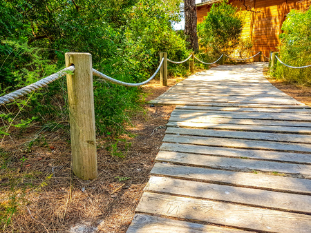 Pedestrian path made with wooden planks on the floor and handrail posts and rope that reach a wooden house Stockfoto