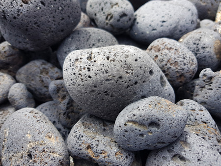 Volcanic rocks rounded by the aleaje of the sea on a beach in Lanzarote, Spain