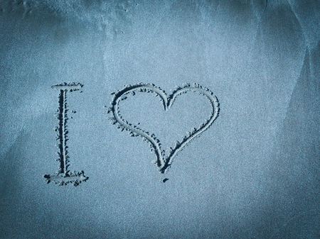 love, written on beach sand and remarked in a very beautiful blue Stockfoto