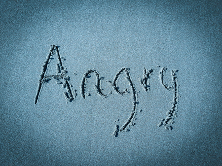 Angry, word written on blue sand