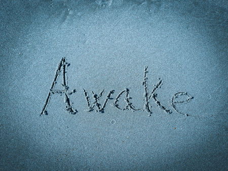 Awake, word written on blue sand