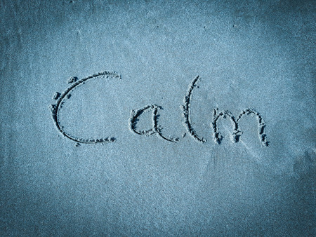 Calm, word written on blue sand