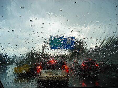 Widok drogi i korków w deszczowy dzień z wnętrza samochodu z mokrą szybą samochodu