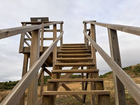 Wooden staircase in a viewpoint of Andelos overlooking the sky. Andelos was a Roman city now in ruins. Located in the town of Mendigorria, Navarra, Spain.