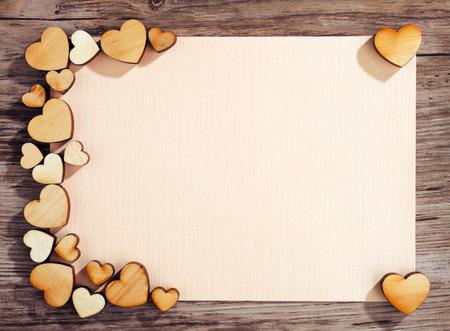wenskaart met een harten en ruimte voor tekst op een houten achtergrond