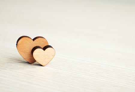 two hearts on a wooden surface with space for text