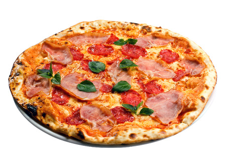 appetizing round pizza with ham, tomatoes and greens Foto de archivo