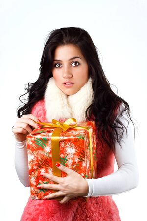 gleeful: beautiful girl with a gift in a pink coat on a white background